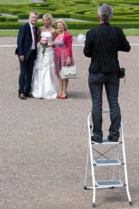 Das Bild zeigt die Fotografin auf einer Leiter, um eine Hochzeitsgesellschaft besser in Szene setzen zu können.