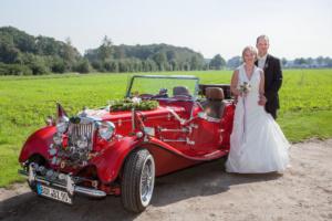 Brautpaar vor einem roten Oldtimer stehend fotografiert von der Fotografin Birgit Giering aus Münster auch bekannt als Lichtgestalterin